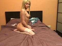 Petite blonde in stockings slowly stripping